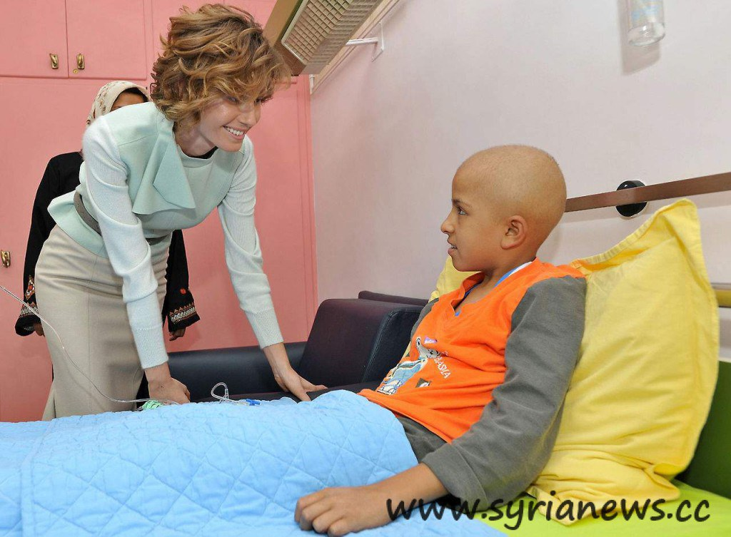 Syria's first lady Asmaa Al-Assad in a visit to a child cancer patient